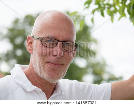 portrait of a mature man with glasses oudoor