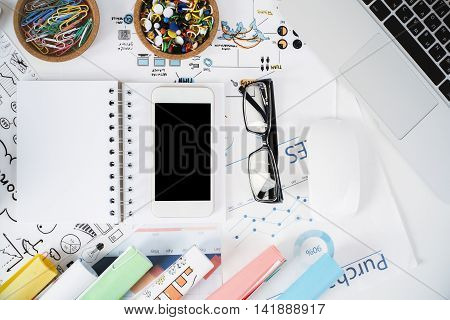 Top view of light office desktop with blank cellular phone spiral notepad glasses business success sketch supplies laptop keyboard and mouse. Mock up