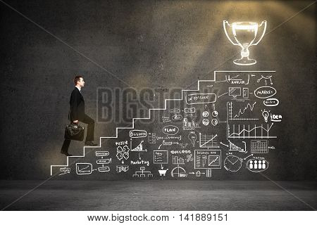 Success concept with businessman climbing abstract ladder and business charts sketch leading to winner's cup on concrete background