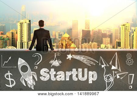 Start up concept with sitting businessman looking at cityscape with sunlight and rocket ship sketch on concrete wall
