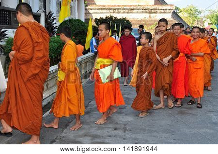 Chiang Mai, Thailand - December 19, 2012:: Barefooted novitiate teenage monks wearing orange robes entering the ubusot sanctuary hall for morning prayer at Wat Chedi Luang
