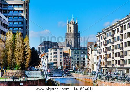 Ghent, Belgium - April 12, 2016: Houses, canal and tower of St Bavo's Cathedral in popular touristic destination Ghent, Belgium