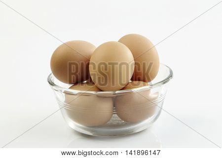 glass bowl full of chicken eggs on the white background