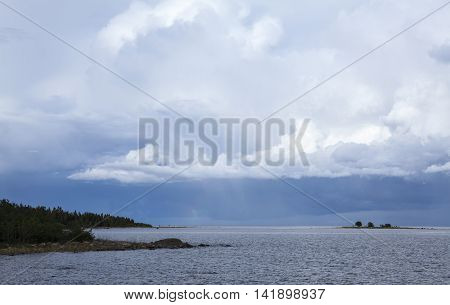 Summer day by the sea. Calm sea, small island, shoreline and clouds in the background. Rain and thunderstorms.