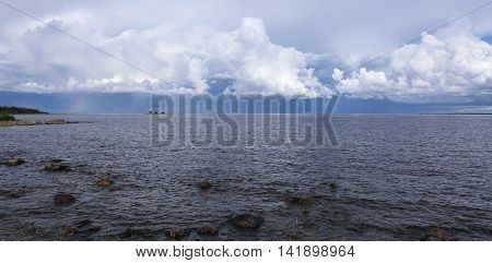 Summer day by the sea. Calm sea, small island and clouds in the background. Rain and thunderstorms. Shore this side.