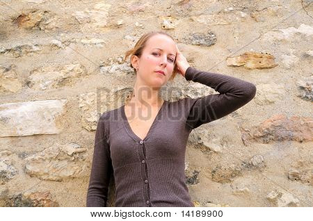Outdoor portrait young woman with brick wall