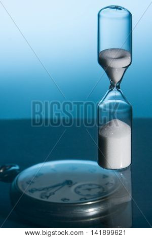Hourglass and pocket watch with blue background