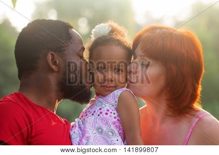 Multiracial mixed family concept. Black father and white mother kissing baby daughter.