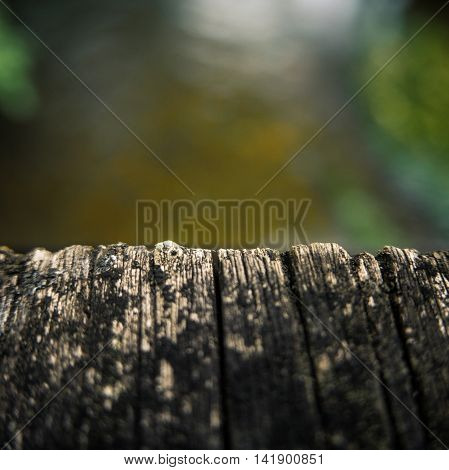 Close-Up Of The Edge Of A Wooden Bridge Over A River With Shallow Depth Of Focus And Copy Space