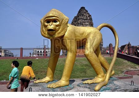 Lopburi Thailand - December 29 2013: An immense gilded monkey sculpture stands outside the gates at historic Khmer Wat Phra Prang Sam Yot