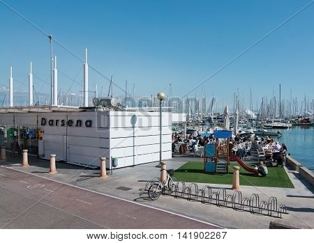 PALMA DE MALLORCA BALEARIC ISLANDS SPAIN - APRIL 2 2016: Darsena outdoor seaside cafe with people in sunshine Palma de Mallorca Balearic islands Spain on April 2 2016.