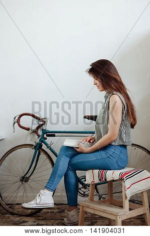 young woman with vintage bicycle reading book at home.