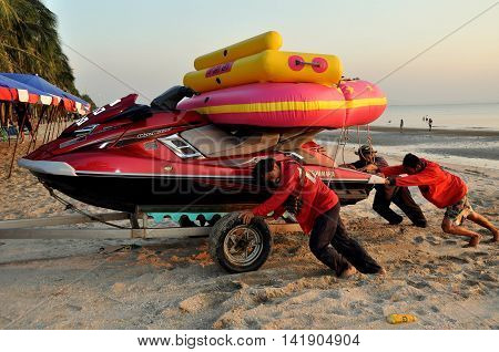 Bang Saen Thailand - January 8 2014: A crew of workers pushes a speed boat and inflated rafts along the beach at the end of the day taking it to storage for the night