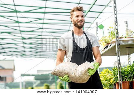 Handsome gardener with apron and working gloves carrying bag with soil for growing plants in the greenhouse