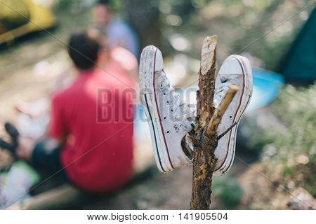 Rest in the woods with friends. Dirty sneakers hanging on a stick at a fire closeup
