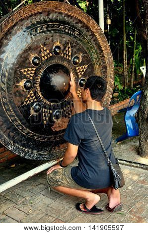 Chiang Mai Thailand - December 19 2012: Thai Buddhist man rubs a large bronze drum for good luck at Wat Phra Singh