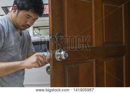locksmith fix the silver knob by screwdriver on wood door - can use to display or montage on products