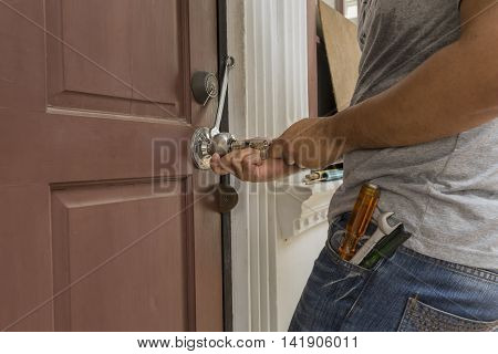 locksmith try to open the wood door by many tools when the key lost - can use to display or montage on products
