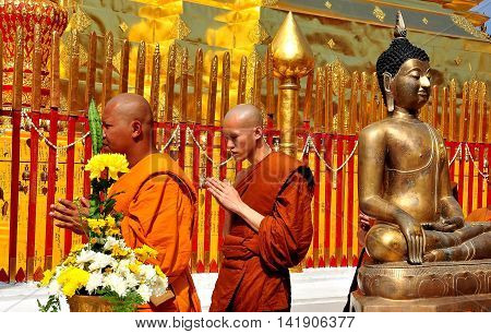 Chiang Mai. Thailand: - December 26 2012: Monks their hands clasped in prayer walking in procession around the golden Chedi at Wat Doi Suthep  *