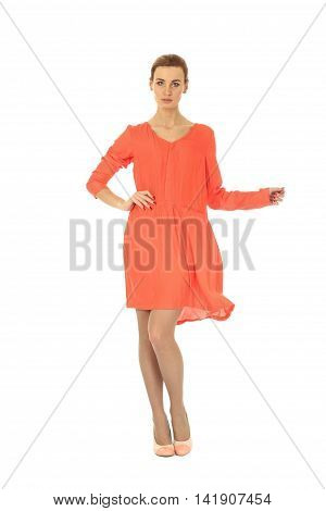 Fashion model wearing coral cocktail dress on white