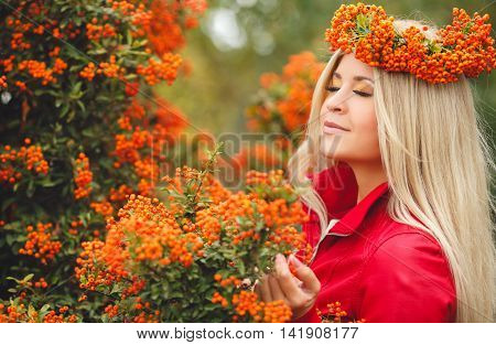 Young beautiful woman with long blonde straight hair,light makeup,wearing a red jacket,on the head wears a wreath of orange of Rowan berries,spending time outdoors in the Park in the middle of autumn,posing near bushes ripe Rowan