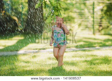 The little baby girl playing with garden sprinkler. Summer outdoor water fun and green grass.