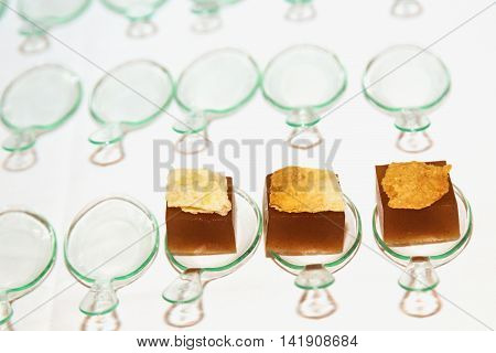 Molecular gastronomy dessert - brown gelatinous cube on a glass spoon