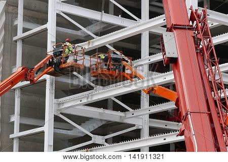 Construction workers stand on platforms as they work on building new shopping center.