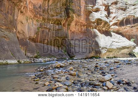 Mid-morning view of water, multi-colored rocks, and cliffs,along The Narrows hiking trail, Zion National Park