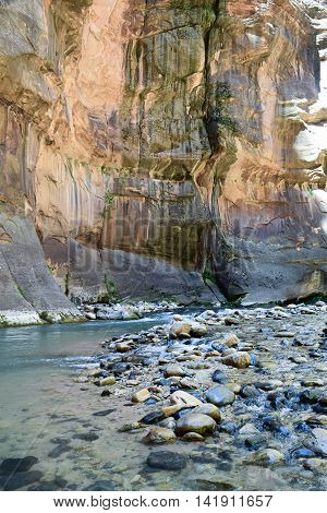 Mid-morning view of a pristine river, multi-colored rocks, and cliffs,along The Narrows hiking trail, Zion National Park