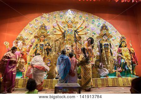 KOLKATA INDIA - OCTOBER 18 2015 : Married Bengali women worshipping Durga idol at Puja pandal shot at colored light at Kolkata West Bengal India. Durga Puja is biggest religious festival of Hinduism.