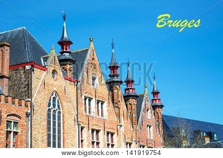 Traditional medieval brick house exterior against blue sky in Brugge, Belguim with city name postcard