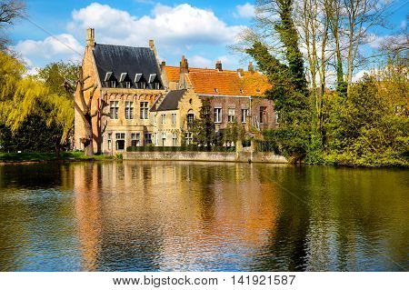 Beautiful view in Bruges, Belgium at Lake of Love, or Minnewater, medieval houses against blue sky