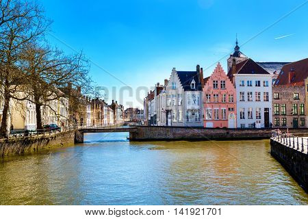 Bruges, Belgium - April 10, 2016: View with canal and colorful traditional houses against cloudy blue sky in popular belgian destination, Brugge, Belguim