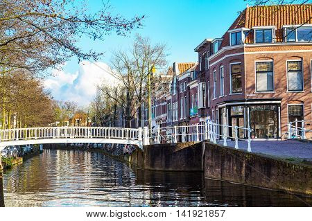 Delft, Netherlands - April 8, 2016: Colorful street view with traditional dutch houses, bicycles, canal in downtown of popular Holland destination