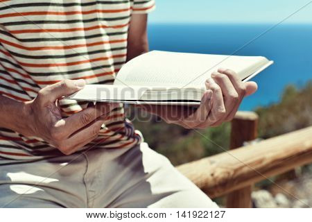closeup of a young caucasian man reading a book outdoors, with the ocean in the background