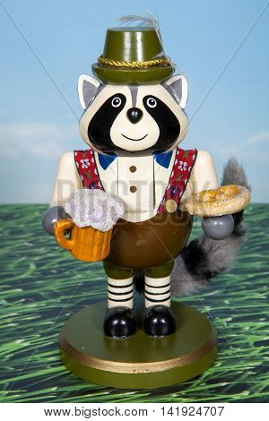 A raccoon holding a beer and pretzel decoration for Oktoberfest