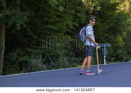 Young men on the road with longboard