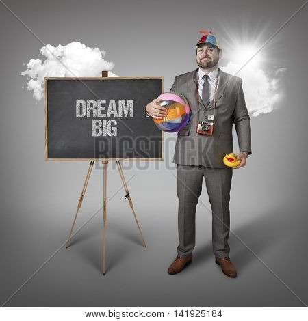Dream big text with holiday gear businessman and blackboard with text
