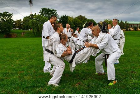 Miskolc Hungary - August 2. 2016: Athletes perform squats using a pertner's weight during the international summer training camp for Kyokushin Karate.