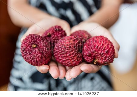 Lychee fruit closeup of woman hands holding asian exotic fruits. Fresh chinese or thai lychees on open palms showing the red skin, that is peeled before eating to reveal a fresh white pulp inside.