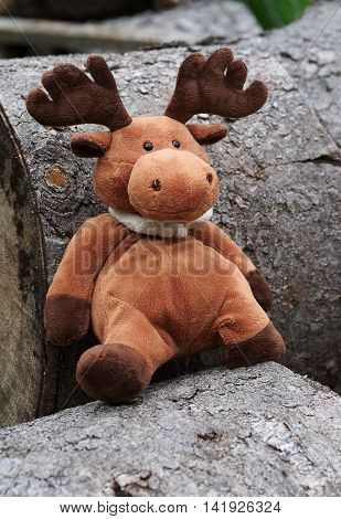 Funny elk toy sits on wood blocks