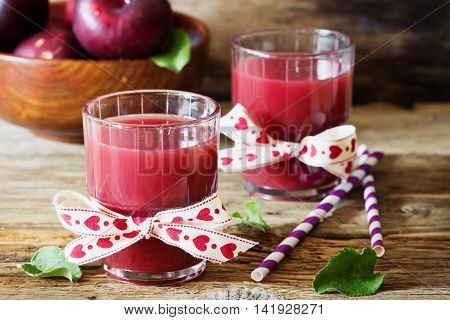 Useful plum juice in a glass on a wooden background. Healthy and diet drink. Selective focus