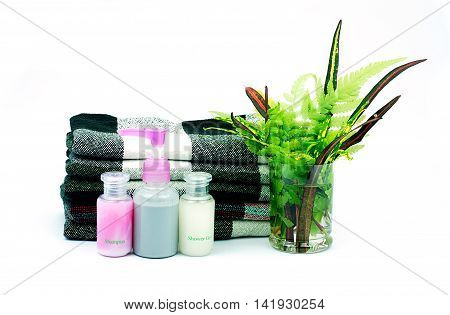 Shampoo and Shower gel bottles and loincloth and green leaves in a glass of water on white background