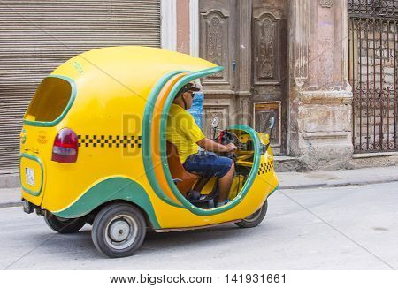 HAVANA CUBA - JULY 18 : A Cocotaxi in old Havana street on July 18 2016. Cocotaxi is an auto rickshaw type taxi vehicle a cheap way to go from one point to the other in Havana.