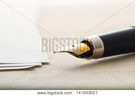 Fountain pen with a sheet of paper on a wooden table.