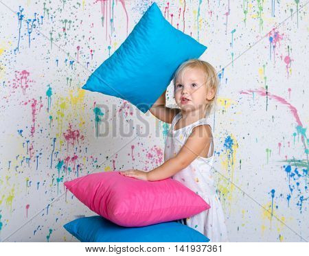 Little girl make the tower from pillows. Photo over colorful wall.