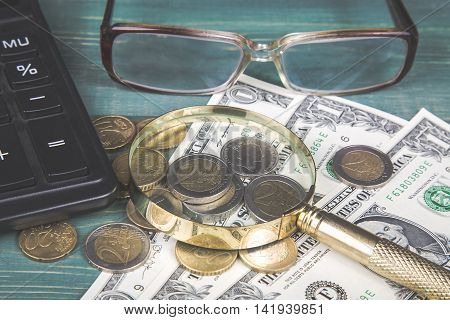 Financial concept. Calculator magnifying glass euro coins british penny dollar bills and glasses on green wood table.