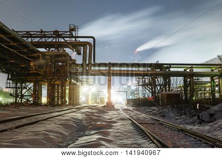 many pipes and smokestacks with industrial tower of metal on the chemical industry at night