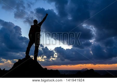 Success achievement running or hiking accomplishment. Business concept with man celebrating with arms up raised outstretched hiking climbing running outdoors. Motivation and inspiration in nature.